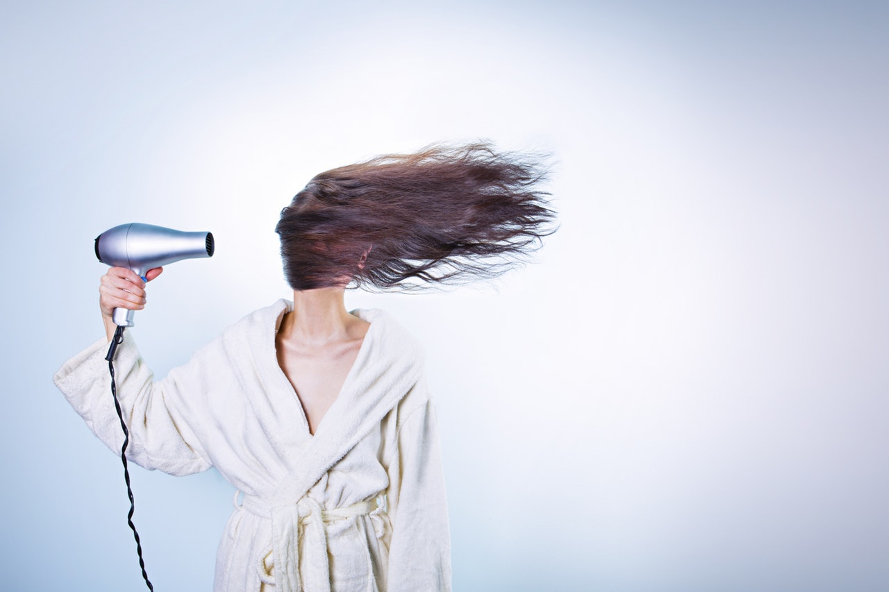 woman wearing bathrobe holding hairdryer
